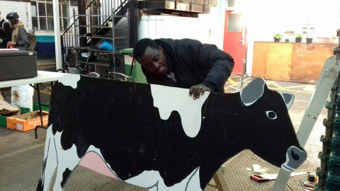 Alex putting the finishes touches to a wooden cow for milking demos
